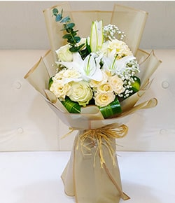 peach roses and white mixed flowers in matching wrapping paper hand bouquet